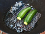 Zucchini on the grilling rack over the hot fire coals