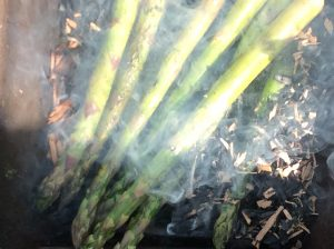 Asparagus cooking directly on the embers