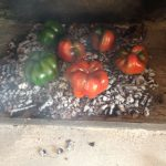 Adding the peppers on top of the bed of coals