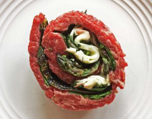 Flank steak pinwheels- all the ingredients are mixed with the flank steak wrapped and tied for grilling.