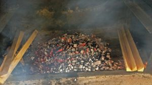 Preparing the bed of embers, keeping extra wood to add during the cooking process