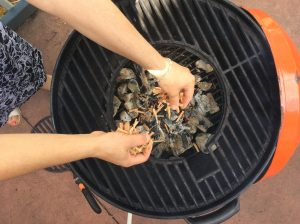 Adding the wood chips to the charcoal fire in our Stok kettle grill