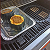 the pan with the squash is placed on the non heated side of the grill, while the heated side has the double filet cherry wood chunks