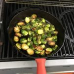 Brussell Sprouts on the grill soaking up the flavors of the cherry wood pieces we added to the grill.