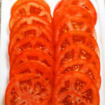 Our thinly sliced fresh red tomatoes on the cutting board are awaiting the assembly of the sandwich