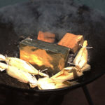 The grill has the Smokinlicious Smoker Wood Chunks around the brick and the snapper wrapped in corn husk on the grill