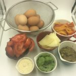 Our simple ingredients for this recipe eggs, tomatoes, parmessan cheese, pesto, bread or Pizza dough