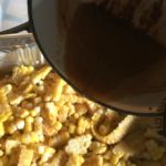 adding the spicy butter to the smoky corn